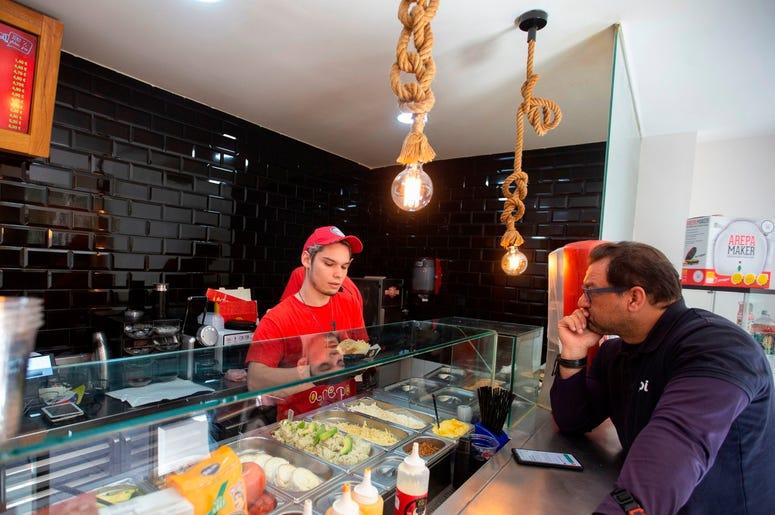 En esta imagen del 19 de junio de 2019, un empleado prepara una arepa para un cliente en el restaurante Arepa Ol en Madrid, Espa a, el mi rcoles 19 de junio de 2019.