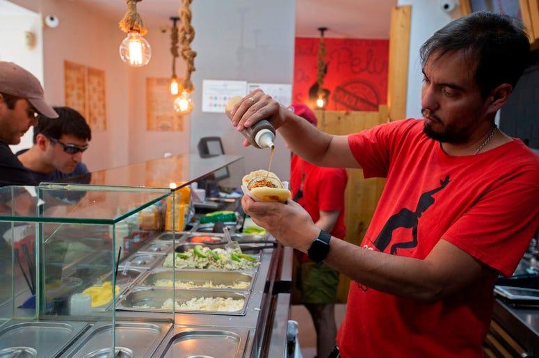 En esta imagen del 19 de junio de 2019, el cocinero y propietario del restaurante Arepa Ol , Edgar Rodr guez, de Venezuela, prepara una Arepa Iberia con jam n serrano, tomate y aceite de oliva en Madrid, Espa a.