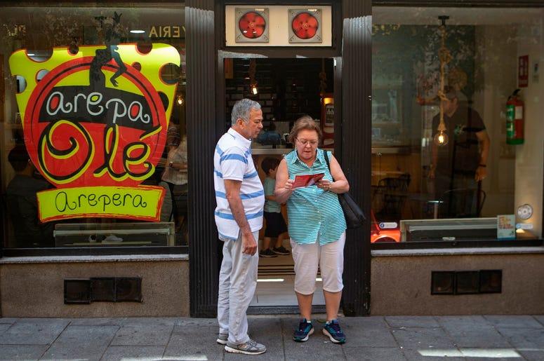 En esta imagen del 19 de junio de 2019, una pareja mira el men ante el restaurante Arepa Olé en Madrid, Espa a, el 19 de junio de 2019.