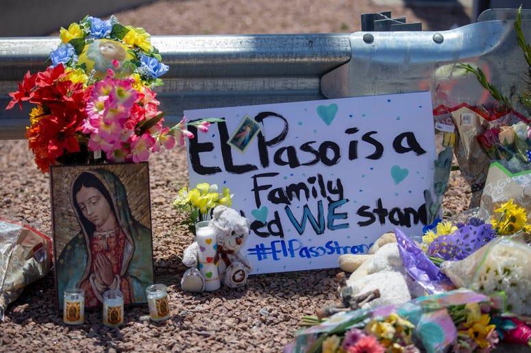 """Flores y una imagen de la Virgen de Guadalupe adornan un monumento conmemorativo improvisado en honor de las víctimas de un tiroteo en un centro comercial en El Paso, TX el 4 de agosto de 2019. El letrero dice """"El Paso es una familia. Permanecemos unidos"""""""