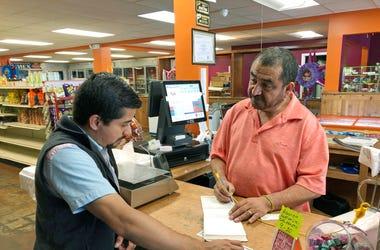 Fotografía del jueves 8 de agosto de 2019 de Juan García, derecha, atendiendo a un cliente en su tienda Hondumex en el centro de Morton, Mississippi.