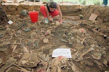 En esta foto de archivo del 23 de octubre de 1992, la antropóloga forense Claudia Bernard, de Argentina, limpia tierra de restos humanos en El Mozote, El Salvador.