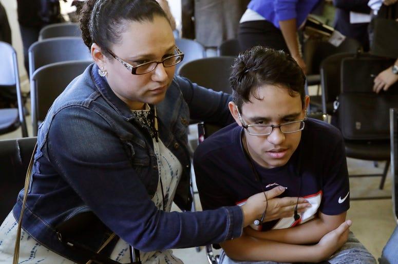La hondureña Mariela Sánchez consuela a su hijo Jonathan, de 16 años, durante una conferencia de prensa, el lunes 26 de agosto del 2019 en Boston. La familia Sánchez viajó a Estados Unidos en busca de tratamiento médico para Jonathan, quien sufre de fibro