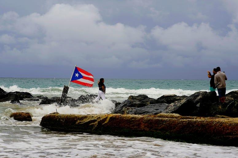 Una mujer posa para una fotografía con el mar y una bandera de Puerto Rico de fondo tras el paso de la tormenta tropical Dorian por la isla, en San Juan, Puerto Rico, el 28 de agosto de 2019.