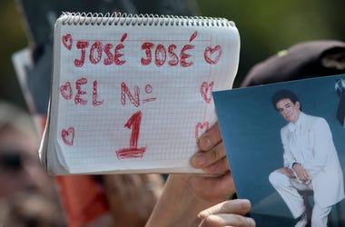 """Un admirador sostiene un cuaderno con el letrero """"José José el No.1"""" junto a una fotografía del fallecido cantante mexicano José José en un homenaje con karaoke en la Ciudad de México el viernes 4 de octubre de 2019. El llamado """"Príncipe de la canción"""" fa"""
