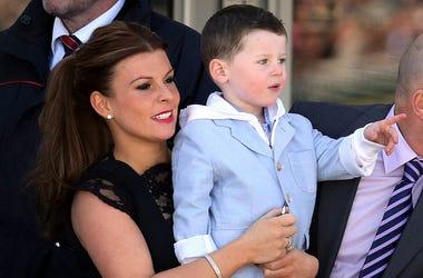 En imagen de archivo del sábado 6 de abril de 2013, Coleen Rooney, izquierda, esposa del futbolista inglés Wayne Rooney, y su hijo Kai, derecha, en Aintree Racecourse, Liverpool, Inglaterra.