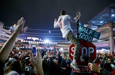 Un aficionado de los Nacionales de Washington escala un poste a las afueras de Nationals Park a primeras horas del jueves 31 de octubre de 2019, en Washington, después de que los Nacionales derrotaron a los Astros de Houston en el séptimo juego de la Seri