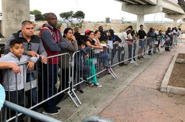 En esta fotografía del 26 de septiembre de 2019, solicitantes de asilo en Tijuana, México, esperan ser nombrados de una lista de espera en un cruce fronterizo en San Diego.