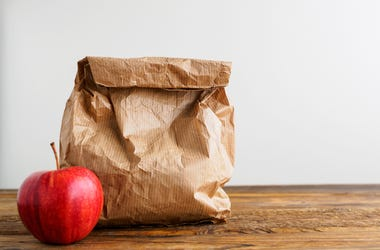 An apple next to brown paper bag lunch
