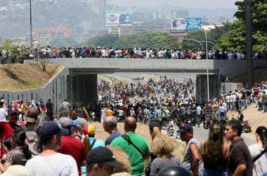 Demonstrators gather near La Carlota air force on April 30, 2019 in Caracas, Venezuela. Through a live broadcast via social media, Venezuelan opposition leader Juan Guaido called for a military uprising against the government of Nicolás Maduro. He declare