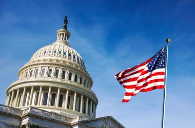 American flag waving with the Capitol Hil