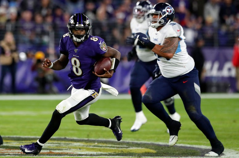 Quarterback Lamar Jackson #8 of the Baltimore Ravens carries the ball against the defense of the Tennessee Titans during the AFC Divisional Playoff game at M&T Bank Stadium on January 11, 2020 in Baltimore, Maryland