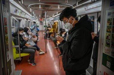A Chinese man wears a protective mask as he stands on the subway during rush hour on February 17, 2020 in Beijing, China.