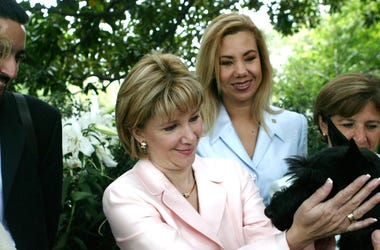Ana Ligia Mixco Sol de Saca (C), wife of President Antonio Saca of El Salvador, greets Barney, the Bush family dog, after having coffee at the White House July 13, 2004 in Washington, DC.