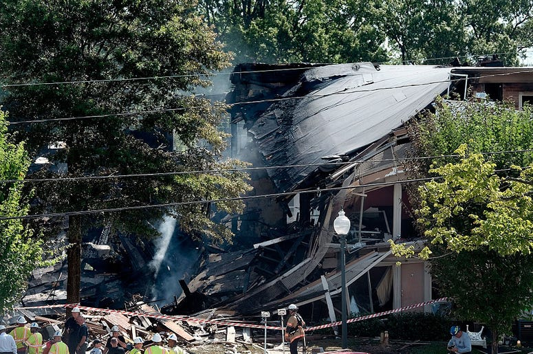 Fire and rescue crews and investigators are seen at the site of an overnight explosion and fire that destroyed an apartment building in the Flower Branch Apartments complex, on August 11, 2016 in Silver Spring, Maryland