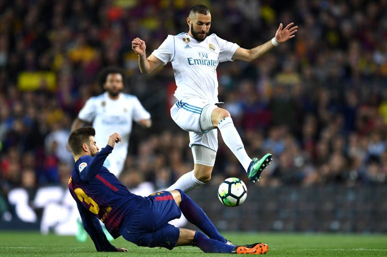 BARCELONA, SPAIN - MAY 06: Karim Benzema of Real Madrid is challenged by Gerard Pique of Barcelona during the La Liga match between Barcelona and Real Madrid at Camp Nou on May 6, 2018 in Barcelona, Spain.