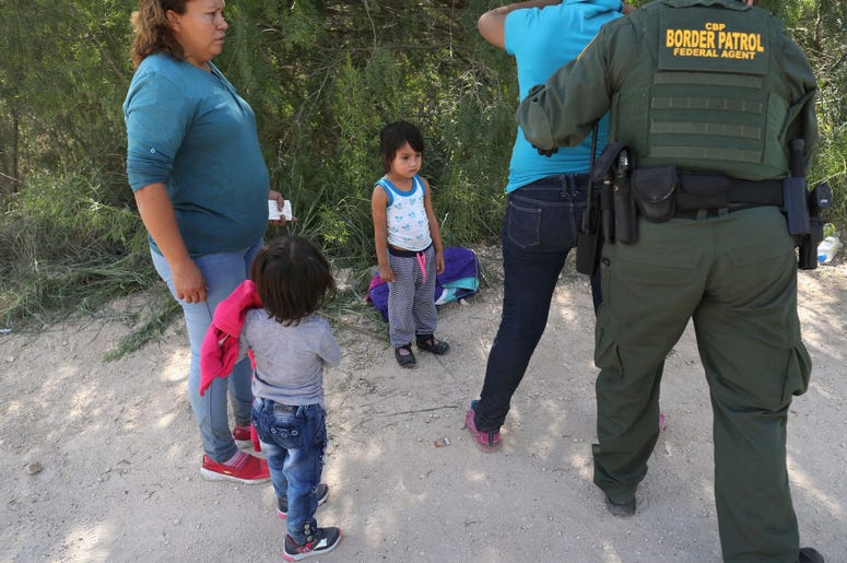Border Patrol agents take Central American asylum seekers into custody on June 12, 2018 near McAllen, Texas. The immigrant families were then sent to a U.S. Customs and Border Protection (CBP) processing center for possible separation. U.S. border author
