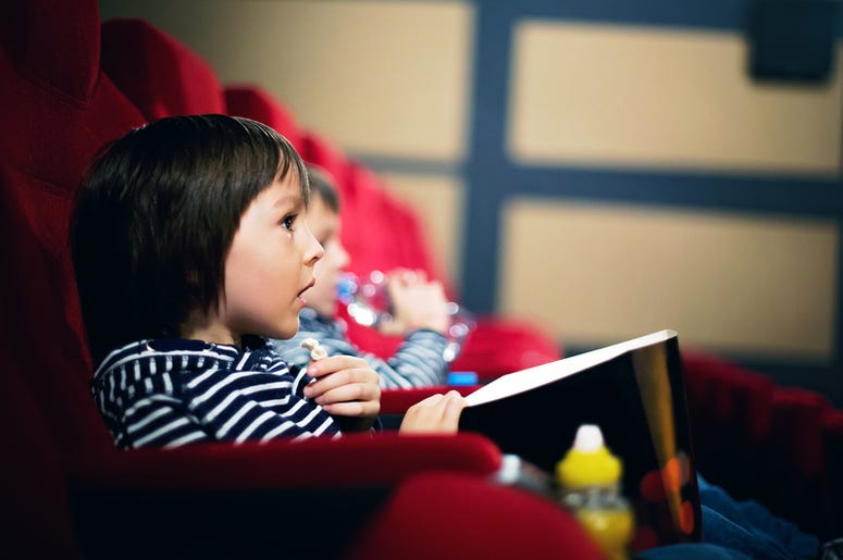 small child eat popcorn in a movie theater
