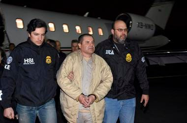 """En esta foto de archivo del 19 de enero de 2017 distribuida por la policía, agentes escoltan al narco mexicano Joaquín """"El Chapo"""" Guzmán, centro, de un avión a una caravana de camionetas en el el aeropuerto MacArthur de Ronkonkoma, Nueva York"""