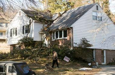 Un hombre pasa por una casa con ramas en el techo en Media, Pensilvania, el lunes 25 de febrero del 2019. Lsa ramas cayeron debido a fuertes vientos.