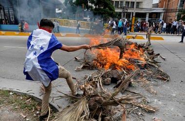 Un manifestante que usa la bandera hondureña como capa arroja madera al fuego durante una protesta en Tegucigalpa, Honduras, el martes 6 de agosto de 2019.