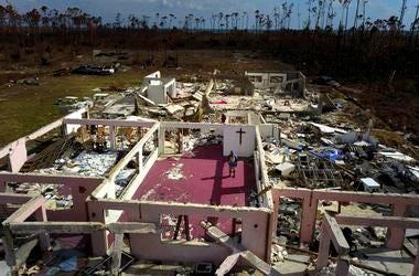 El pastor Jeremiah Saunders posa para una fotografía entre las ruinas de su iglesia, destruida tras el paso del huracán Dorian, en High Rock, Gran Bahama, Bahamas, el 11 de septiembre de 2019.