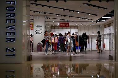 En esta imagen de archivo del martes 7 de mayo de 2019, mujeres mirando ropa en una tienda de la minorista estadounidense Forever 21, que ofrecía descuentos por liquidación en un centro comercial tras anunciar su salida del mercado chino, en Beijing.