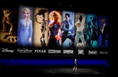 En esta foto del 3 de abril de 2019, personajes de cintas de Disney y Fox se proyectan detrás de Cathleen Taff, una ejecutiva de Walt Disney Studios, durante la presentación de Walt Disney Studios Motion Pictures en CinemaCon 2019 en Las Vegas. Verizon es