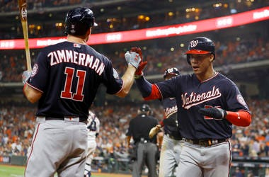 El dominicano Juan Soto festeja con Ryan Zimmerman, su compañero en los Nacionales de Washington, tras anotar en un hit de Asdrúbal Cabrera durante el segundo juego de la Serie Mundial ante los Astros de Houston, el miércoles 23 de octubre de 2019
