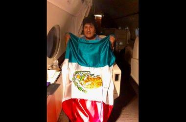 En esta imagen publicada por el ministro mexicano de Exteriores, Marcelo Ebrard, se ve al expresidente de Bolivia Evo Morales sosteniendo una bandera mexicana a bordo de un avión de la Fuerza Aérea mexicana, el lunes 11 de noviembre de 2019. protests.
