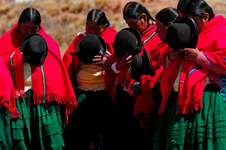 Mujeres aymaras rezan antes de que inicie una excavación para extraer vasijas prehispánicas en el templo de Kalasayaya en la antigua ciudad de Tiwanaku, Bolivia, el miércoles 19 de septiembre de 2019.