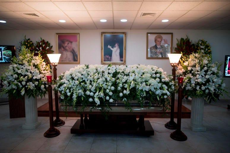 El ataúd con los restos del astrólogo de la televisión Walter Mercado, cubierto de lilas y rosas, es exhibido durante un velatorio público en el vecindario de Santurce, en San Juan, Puerto Rico, el miércoles 6 de noviembre de 2019.