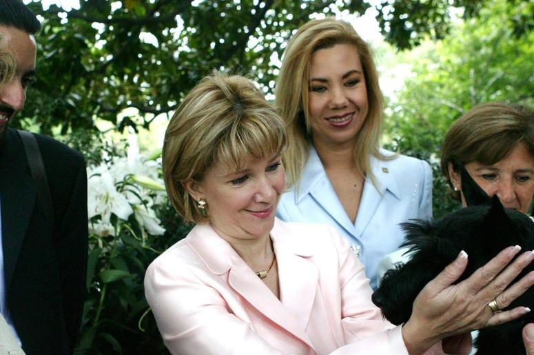 Ana Ligia Mixco Sol de Saca (C), wife of President Antonio Saca of El Salvador, greets Barney, the Bush family dog, after having coffee at the White House July 13, 2004 in Washington, DC.