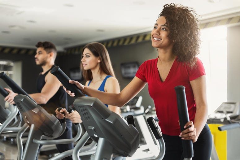 Young people exercising on cardio stepper in gym