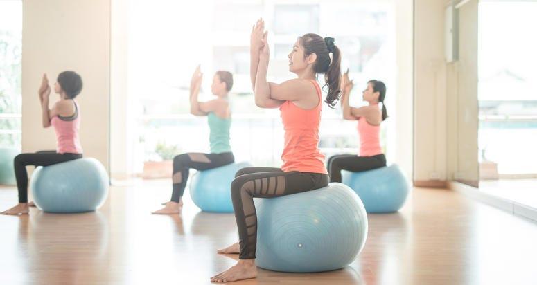 woman stretching on yoga ball in gym .do yoga