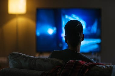 Back View of a Man Sitting on a Couch Watching Movie on His Big Flat Screen TV