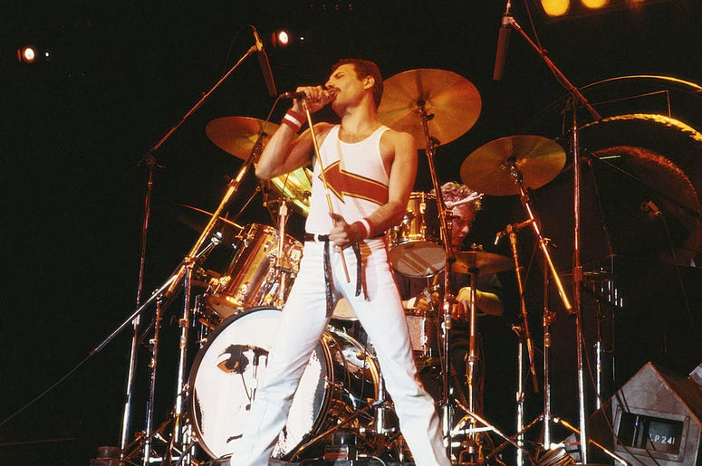 Freddie Mercury (1946-1991), singer with Queen, standing in front of a drumkit as he sings into a microphone on stage during a live concert performance by the band at the National Bowl in Milton Keynes, England, United Kingdom, on 5 June 1982.