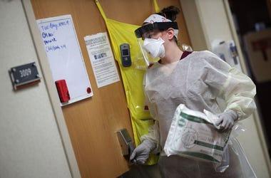Nurses prepares to enter a COVID-19 patient's room