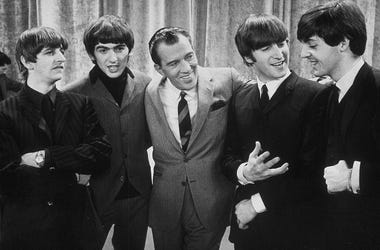 American television host Ed Sullivan smiles while standing with British rock group the Beatles on the set of his television variety series, New York, February 9, 1964. Left to right: Ringo Starr, George Harrison, Sullivan, John Lennon, Paul McCartney.