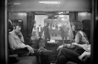 25th August 1967: Paul McCartney of the Beatles and Mick Jagger of the Rolling Stones sit opposite each other on a train at Euston Station, waiting for departure to Bangor. (Photo by Victor Blackman/Express/Getty Images)