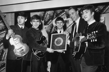 The Beatles holding their silver disc. Left to right are, Paul McCartney, George Harrison (1943 - 2001), Ringo Starr, George Martin of EMI and John Lennon (1940 - 1980).