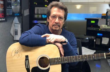Michael Stanley with a signed acoustic guitar