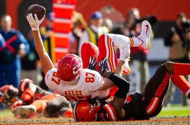 Kansas City Chiefs tight end Travis Kelce (87) raises the ball as he scores a touchdown while being tackled by Cleveland Browns outside linebacker Christian Kirksey (58) during the second quarter at FirstEnergy Stadium.