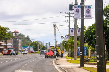 Guam Power Authority employees utilized the basket of a bucket truck to hang 75th Liberation banners, on utility poles along Marine Corps Drive, in H gat a on Tuesday, July 16, 2019. The section of the roadway is part of the Liberation Day Parade route sl