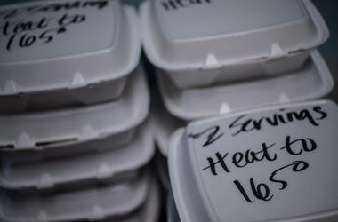 As MLK Center staff dish out prepared food into containers, reheating instructions are written on top of each meal to ensure food safety on Friday, March 27, 2020. Mlk Center Coronavirus Help Food Delivery