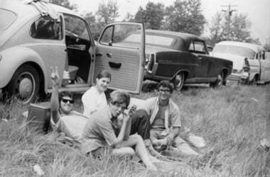 A group of friends sitting by their car at the Woodstock Music and Arts Fair, one of them is giving a peace sign
