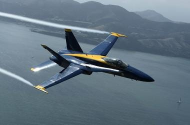 A U.S. Navy Blue Angels F/A-18 Hornet piloted by U.S. Marine Corps Major Nathan Miller flies over the San Francisco Bay