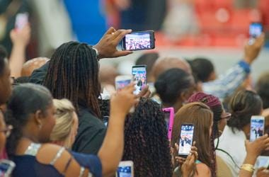 Relatives and friends take photographs with their Relatives and friends take photographs with their smart phosmart phones of graduating seniors marching into Broadbent Arena during the school's commencement exercises. 12 June 2019 0612ferncreekgrad011 Drl