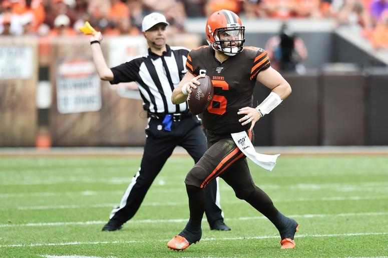 Cleveland Browns quarterback Baker Mayfield (6) scrambles as field judge Michael Banks (72) throws a penalty flag during the second half against the Tennessee Titans at FirstEnergy Stadium.