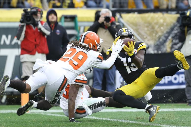 Pittsburgh Steelers wide receiver James Washington (13) catches a touchdown pass against Cleveland Browns defensive back T.J. Carrie (rear) and defensive back Sheldrick Redwine (29) during the second quarter at Heinz Field.